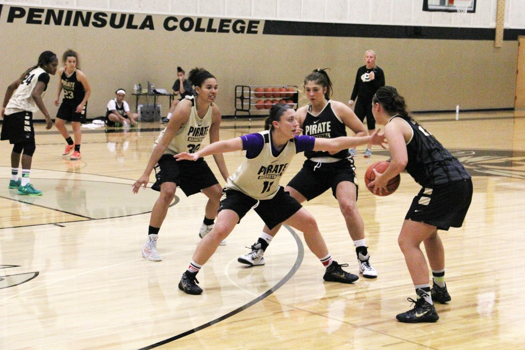 Cierra Moss, middle, guarding her sister Cherish Moss during practice. - Photo by Eric Trent.